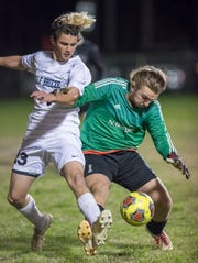 Zack Thompson (23) and Raiders goalie Korey Betts (1) fight for a loose ball during the Gulf Breeze vs Navarre boys soccer game in Navarre on Friday, Jan. 17, 2020.