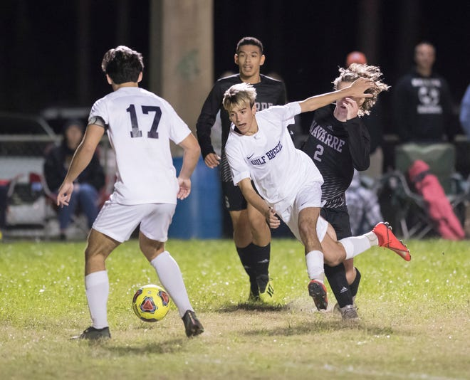 Anthony Ciccarello (14) gets tripped while controlling the ball during the Gulf Breeze vs Navarre boys soccer game in Navarre on Friday, Jan. 17, 2020.