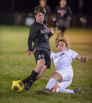 Owen Eble (24) and Keegan Abell (3) fight for the ball during the Gulf Breeze vs Navarre boys soccer game in Navarre on Friday, Jan. 17, 2020.