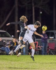 Brady Ackman (2) and Jayce Dotson (17) vie for the ball during the Gulf Breeze vs Navarre boys soccer game in Navarre on Friday, Jan. 17, 2020.