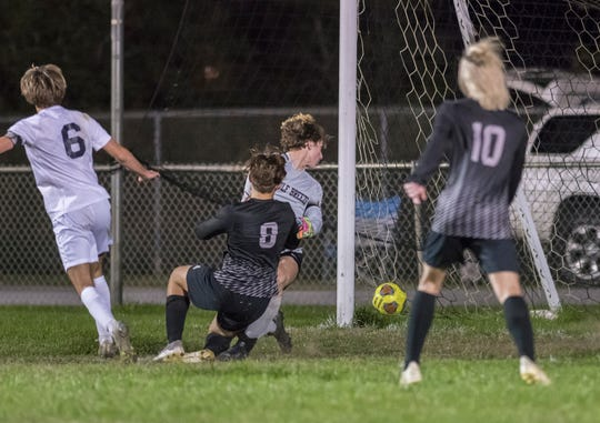 Sean Isari (8)'s kick gets past Dolphins goalie Trevor Isakson (1) as the Raiders take a 1-0 lead during the Gulf Breeze vs Navarre boys soccer game in Navarre on Friday, Jan. 17, 2020.