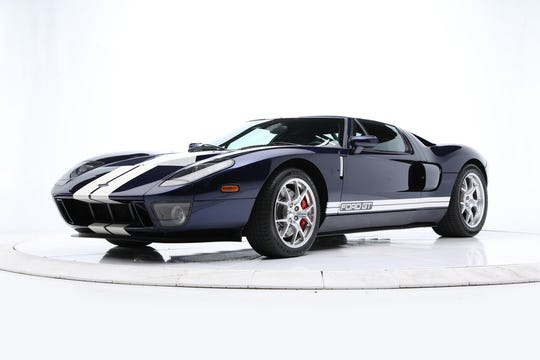 This Ford GT comes with thick white racing stripes on midnight blue paint with red brake calipers, lightweight forged aluminum wheels and McIntosh sound.