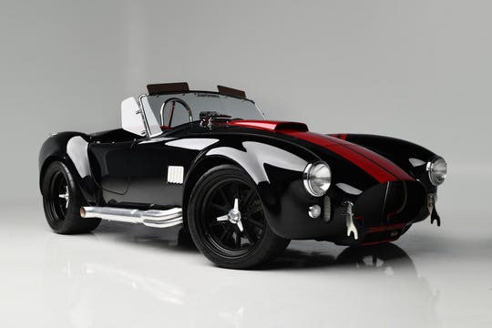 This Superformance MKIII Roadster has deep-red racing stripes on a black replica of a 1965 Shelby Cobra.