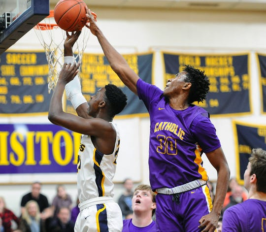 Elco's Asher Kemble (24) gets his shot blocked by Lancaster Catholic's David Kamwanga (30) during the first quarter of play.