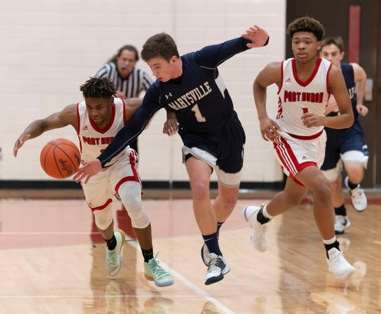 Port Huron's Nijere Finney and Marysville's Evan Woodard scramble for a loose ball Friday, Jan. 17 during their basketball game at Port Huron High School.