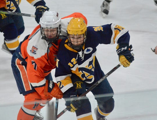 Port Huron Northern's Chad Noetzel battles for the puck against Flint Powers Catholic during a hockey game on Saturday, Jan. 18, 2020, at Flint Iceland Arenas