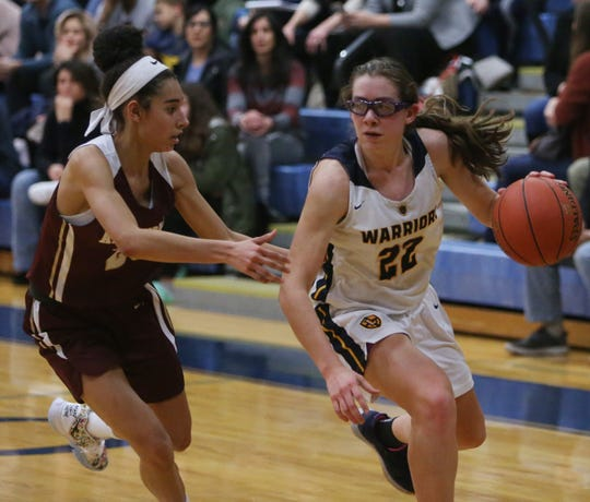 Lourdes' Sofia Feigelson drives against Arlington's Mia Castillo during a girls basketball game on Jan. 17.