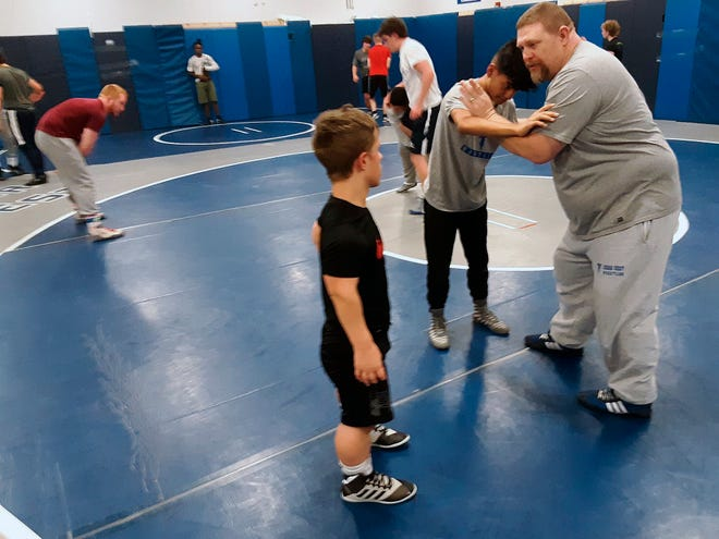 Cedar Crest wrestling coach Chris Voshell instructs Bailey Pennypacker, left, and a teammate during a recent practice. (Pat Huggins/Lebanon Daily News via AP)