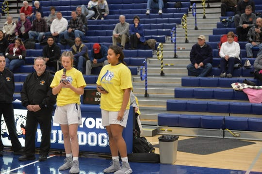 Juniors Dorian Ilyes (left) and Jillian Foster (right) give a speech on down syndrome before the varsity girl's basketball game.