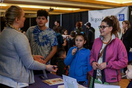Maria Deal Torre, of Salem, speaks to a vendor at the Kroc Center's annual health fair in Salem on Jan. 18, 2020.