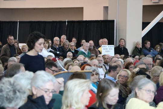 """Joy Weber, development manager for Orsted speaks at the podium while an onlooker holds a """"Don't screw with our view"""" sign in the back of the room. Weber and Orsted are currently planning to build a wind farm off the coast of Maryland and Delaware."""