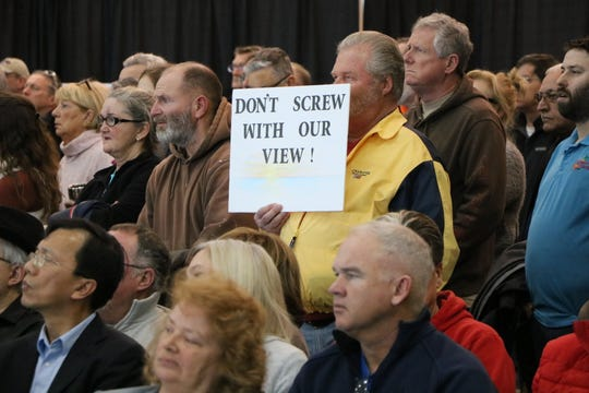 "A member of the audience holds up a sign saying ""Don't Screw With Our View"" during the Maryland Public Service Commission's public hearing on offshore wind on January 18, 2020 at the Ocean City Convention Center."