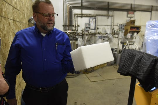 Dean Boese, Central McGowan's dry ice expert, holds a block of dry ice made from compressed dry ice rice. Its texture resembles that of Styrofoam.
