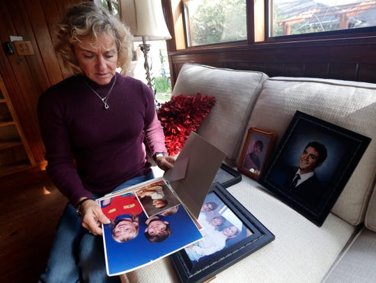 Katherine Gilbert, who is the mother of Justin Joseph Dousa-Valdez, 36, who struggled with mental illness and killed himself in November 2019, looks through old family photos of her children.