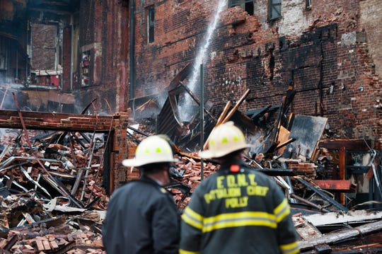 In this file photo, New York City firefighters survey the site of a building explosion in the East Village neighborhood of New York, Friday, March 27, 2015.  Nineteen people were injured, four critically, after the powerful blast and fire sent flames soaring and debris flying. A gas explosion amid plumbing and gas work inside the building was to blame. (AP Photo/The New York Times, Nancy Borowick, Pool)