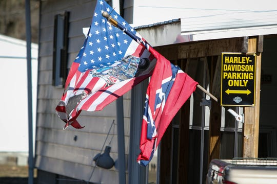 """Confederate and American flags fly on a house down the road from the listed residence of William Bilbrough IV, who was arrested Thursday. Federal agents say he is part of a """"violent"""" white supremacist group."""