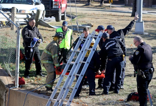 First responders lift a man involved in a single car wreck out of a canal Saturday, Jan. 18, 2020, at the intersection of Midwestern Parkway and Cedar Elm.