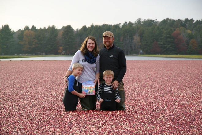 The Detlefsen family poses in 2015 with Lisl's first published book, Time for Cranberries while standing in a flooded bog at their farm family-owned cranberry marsh near Wisconsin Rapids.