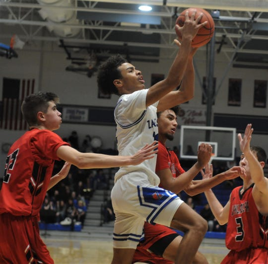 Zanesville's Isaac Mayle drives past a trio of New Philadelphia defenders in the first half of Friday's game. The Quakers won 56-42.