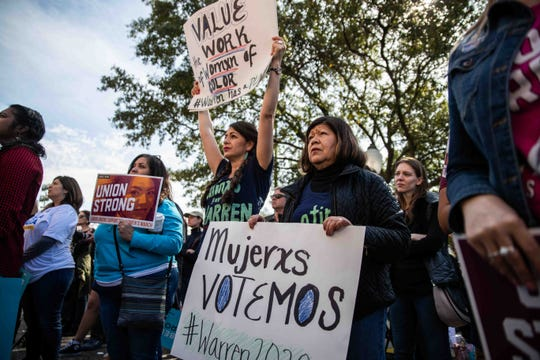 From left, Angelita Guerra, Julieta Garibay and Cecilia Hernandez hold posters supporting women and Elizabeth Warren at the Women's March ATX at the Capitol of Texas in Austin on Saturday, Jan. 18, 2020.