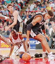 San Antonio Spurs forward J.R. Reid, right, Denver Nuggets forward Reggie Williams, center, and Spurs guard Vinny Del Negro scramble for a loose ball during the Spurs 111-97 victory in Denver on Wednesday, Dec. 21, 1994.