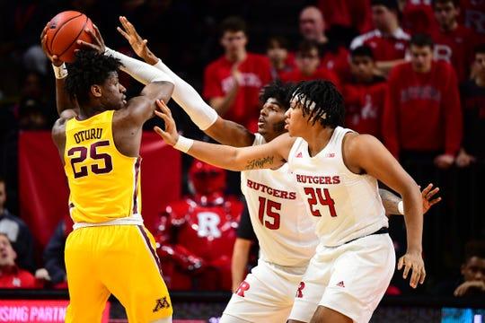 Rutgers' Myles Johnson and Ron Harper Jr. defend Minnesota's Daniel Oturu