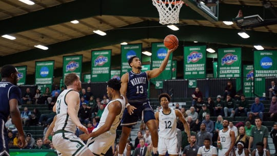 Monmouth's Marcus McClary scores two of his 13 points in a 65-58 victory at Manhattan on Saturday night.