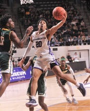 ACU's Coryon Mason (20) drives to the basket against Southeastern Louisana's LaQuan Butler. Mason scored and was fouled by Butler on the play. He hit the free throws to complete the three-point play to give ACU a 48-20 lead with 16:50 left in the game. ACU beat the Lions 76-55 in the Southland Conference game Saturday, Jan. 18, 2020, at Moody Coliseum.