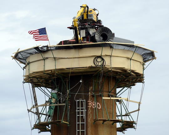 A special machine called the Mantis sits on top of stack 1 at the Duke Energy Skyland power plant. The machine dismantles stacks from the top by knocking small sections of the concrete inward.