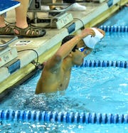 Aaron Sequeira of Walnut Hills pulls off the cap and celebrates his pool record first-place finish of 46.71 seconds in the boys 100-yard backstroke at the 2020 Southwest Ohio Swimming and Diving Classic, Jan. 18, 2020.