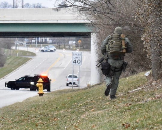 The Hamilton County SWAT team and local law enforcement investigate an incident Sunday atKemper Road and the Interstate 71 overpass.