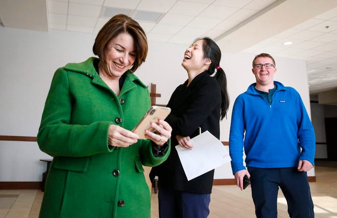 U.S. Sen. Amy Klobuchar makes a joke about making funny faces to engage her facial recognition option on her iPhone as members of her staff around her laugh on Jan. 18, 2020 in Dayton, Ohio.