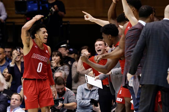 Louisville guard Lamarr Kimble (0) celebrates with the bench at the end of the team's game against Duke Saturday. Louisville won 79-73.