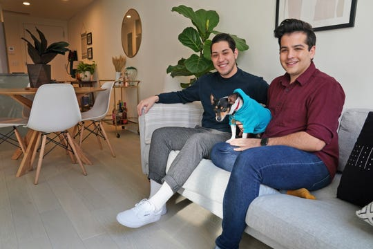 Zachariah Mohammed, left, Pete Mancilla, and their dog Remy in their New York apartment. Most of the furniture including the couch, the table and chairs, the side table and the bar cart, are rented.