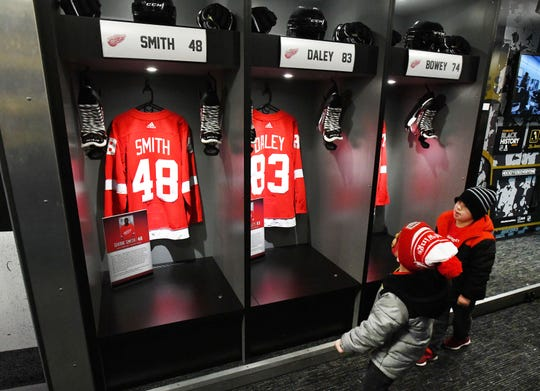 Dekker Kokenyesdi, 5, and Lincoln Kokenyesdi, 6, of Sterling Heights wander through the NHL Black Hockey History Tour bus outside Little Caesars Arena including a display with the current African American players on the Detroit Red Wings: Givani Smith, Trevor Daley and Madison Bowey.