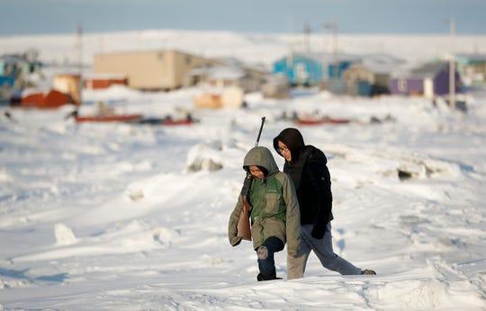 George Chakuchin, left, and Mick Chakuchin walk on ice over the Bering Sea Saturday, Jan. 18, 2020, in Toksook Bay, Alaska.