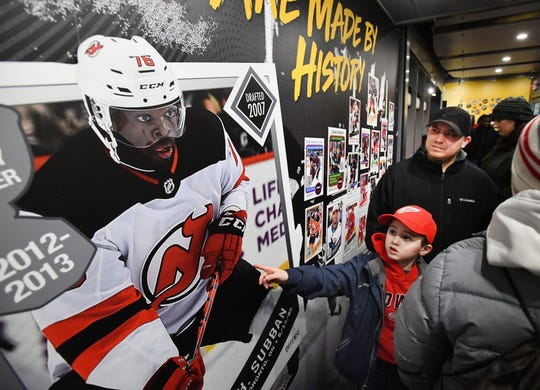 Noah Mesi, 6, points out New Jersey Devils P.K. Subban to his dad Nick Mesi of Westland as they walk through the NHL Black Hockey History Tour bus outside Little Caesars Arena in Detroit on January 19, 2020.