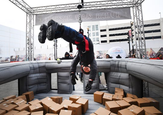 Gavin Davis, 6 of Rochester Hills hangs upside down, trying to grab a box prize at the Human Claw Machine outside of Little Caesars Arena.