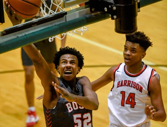 Bosse's Kiyron Powell (52) drives past Harrison's Kevin Langley (14) as the Bosse Bulldogs play the Harrison Warriors in the boys Southern Indiana Athletic Conference tournament championship Saturday evening at North High, January 18, 2020.
