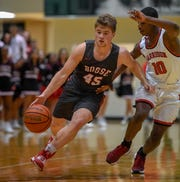 Bosse's Kolten Sanford (45) drives the ball against Harrison's Treyvone Hooks (10) as the Bosse Bulldogs play the Harrison Warriors in the boys Southern Indiana Athletic Conference tournament championship Saturday evening at North High, January 18, 2020.