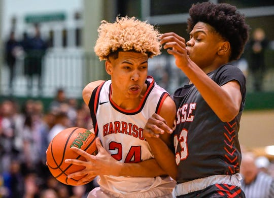 Harrison's Jahni Summers (24) drives against Bosse's Julian Norris (23) as the Bosse Bulldogs play the Harrison Warriors in the boys Southern Indiana Athletic Conference tournament championship Saturday evening at North High, January 18, 2020.