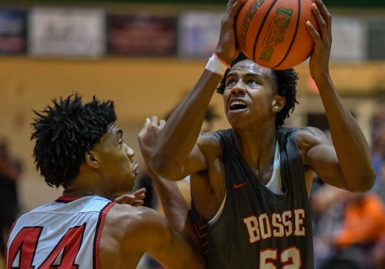 Bosse's Kiyron Powell (52) looks to shoot over Harrison's Terrence Ringo Jr. (44) as the Bosse Bulldogs play the Harrison Warriors in the boys Southern Indiana Athletic Conference tournament championship Saturday evening at North High, January 18, 2020.