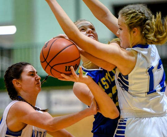 Castle's Natalie Niehaus (32) shoot against defensive pressure from Memorial's Mallory Russell (32) and Peyton Murphy (12) as the Memorial Tigers play the Castle Knights in the girls Southern Indiana Athletic Conference tournament championship Saturday evening at North High, January 18, 2020.