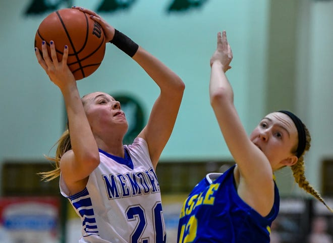 Memorial's Ryeligh Anslinger (20) shoots over Castle's Keira Moore (12) as the Memorial Tigers play the Castle Knights in the girls Southern Indiana Athletic Conference tournament championship Saturday evening at North High, January 18, 2020.