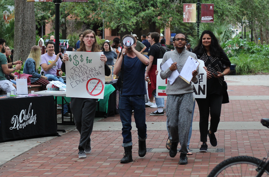 Protestors walk down Legacy Walk chanting and talking to students about their organization.