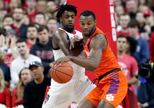 North Carolina State's D.J. Funderburk (0) defends Clemson's Aamir Simms (25) during the first half of an NCAA college basketball game at PNC Arena in Raleigh, N.C., Saturday, Jan. 18, 2020. (Ethan Hyman/The News & Observer via AP)