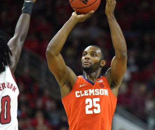 Jan 18, 2020; Raleigh, North Carolina, USA; Clemson Tigers forward Aamir Simms (25) shoots over North Carolina State Wolfpack forward DJ Funderburk (0) during the second half at PNC Arena. Mandatory Credit: Rob Kinnan-USA TODAY Sports