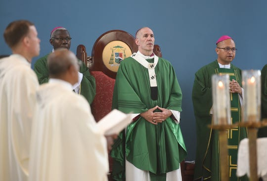 Archbishop Michael J. Byrnes, center, after receiving a pallium at the Dulce Nombre de Maria Cathedral-Basilica, is shown in this Jan. 19 file photo.