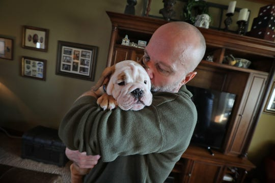 "Butler Blue IV, aka ""Blue,"" the next Butler Bulldog mascot, snuggles with Indy Star Sports columnist Gregg Doyel at the Madaj home in Greenwood, Thursday, Jan. 16, 2020.  Butler Blue III, aka ""Trip,"" and Trip's handler Michael Kaltenmark, are retiring from their mascot and handler jobs in May 2020. Evan Krauss and Blue will be the next handler and Butler mascot."