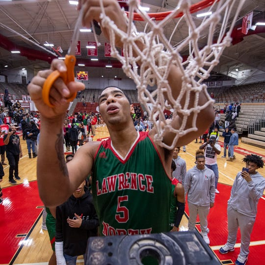 Lawrence North High School junior DJ Hughes (5) cuts down a piece of the game net after winning the championship game in the 2020 Marion County Boys' Basketball Tournament against Lawrence Central High School, Saturday, Jan. 18, 2020, at Southport High School. Lawrence North won 51-46.